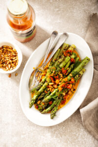 Gegrilde groene asperges met wortel-knoflookjus, dille en pijnboompitten groentesap